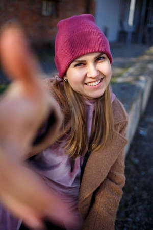 stylish girl model in a brown coat, pink suit and pink hat smiles beautifully. The trends of modern fashion. Fashionable image. Bright emotions Archivio Fotografico