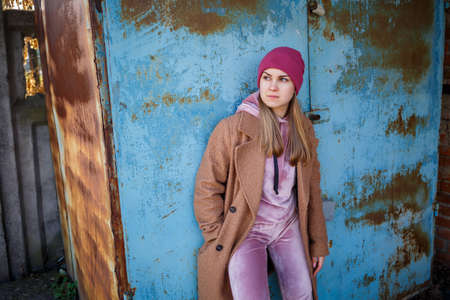 stylish girl model in a brown coat, pink suit and pink hat smiles beautifully. The trends of modern fashion. Fashionable image. Bright emotions 版權商用圖片