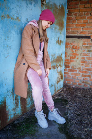 stylish girl model in a brown coat, pink suit and gray boots on the city ruins. The trends of modern fashion. Fashionable image 版權商用圖片