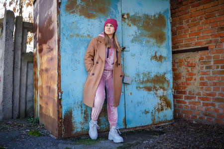 stylish girl model in a brown coat, pink suit and gray boots on the city ruins. The trends of modern fashion. Fashionable image Archivio Fotografico