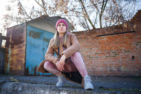 stylish girl model in a brown coat, pink suit and gray boots on the city ruins. The trends of modern fashion. Fashionable image