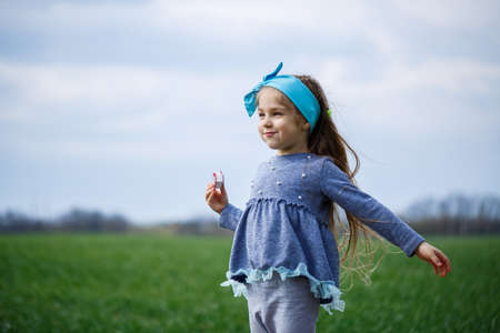 little girl child runs and jumps, green grass in the field, sunny spring weather, smile and joy of the child, blue sky with clouds