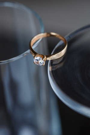 A wedding ring made of precious metal with a diamond stone lies in a glass Foto de archivo