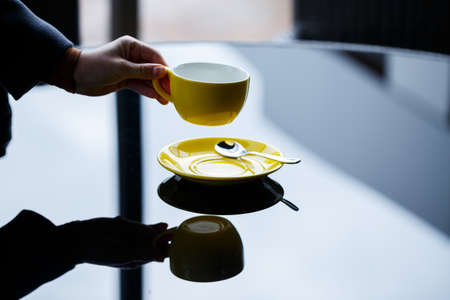 Yellow cup for coffee or tea with a saucer in the hands of a girl on the background of a glass table.