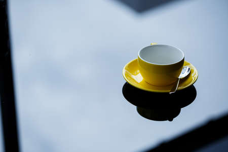 Yellow cup for coffee or tea with a saucer on a glass table.