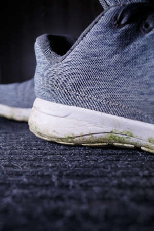 Gray men's sneakers with a dirty sole from the earth and grass, shoes for jogging and sports