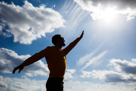 guy tourist freelancer on a background of blue sky with white clouds, bright sunny day, nature and human freedom 免版税图像