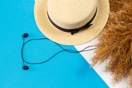 Female accessories headphones, hat, lifestyle, woman, rest, with dry grass, decor, flat lay, color style in the background. Travel, tourism concept. Beach accessories top view. Imagens