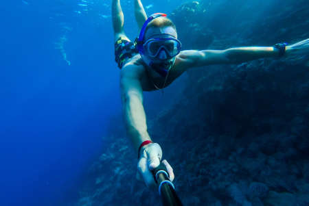 A guy with a mask and snorkel dives into the blue water of the Red Sea and photographs himself