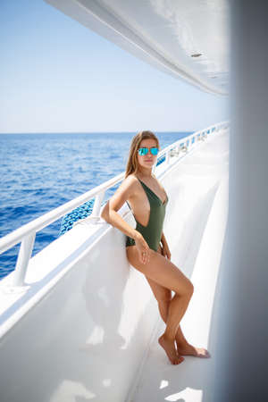 A girl with a beautiful figure in a green swimwear. She is on a white yacht in the red sea