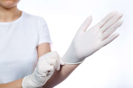 Girl paramedic puts on white medical gloves on hands. Protection against germs and viruses. She is in a white T-shirt on a white background. Banco de Imagens