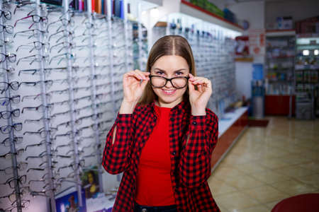 A visually impaired girl chooses glasses. She is wearing a shirt and a beautiful smile.