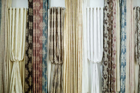Curtain samples hanging from hangers on rail in store. Fabric texture samples selection fabrics for interior decoration Curtains, tulle and furniture upholstery. Zdjęcie Seryjne