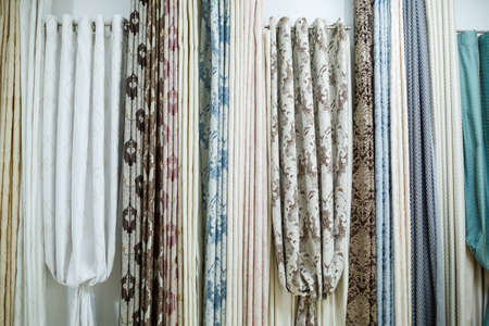 Curtain samples hanging from hangers on rail in store. Fabric texture samples selection fabrics for interior decoration Curtains, tulle and furniture upholstery. Banco de Imagens