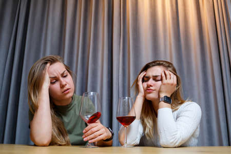 A woman consoles a sad depressed friend who needs help. Depression with alcohol concept. upset young girl with unhappy face holding a glass of wine looking at her best sister