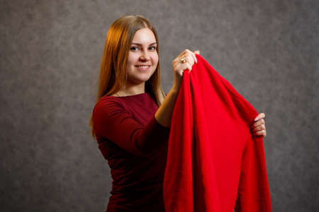 beautiful girl tries on a red sweater