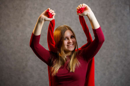 Girl tries on a red sweater on a gray background