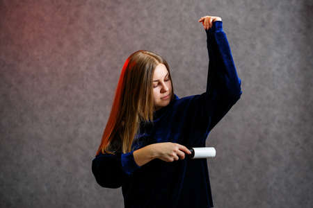 Girl cleans a sweater with a special roller with adhesive tape