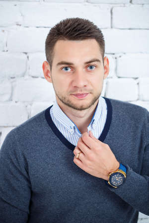 young guy in a shirt and sweater against a white brick wall Stockfoto