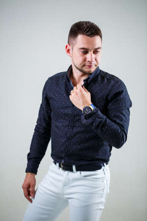 Young businessman guy in black shirt and white trousers on a white background