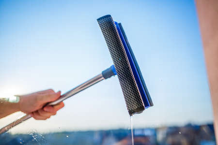 Window cleaning in high-rise buildings, houses with a brush. Window cleaning brush. Large window in a multi-storey building, cleaning service. Dust removal and glass washing. Imagens