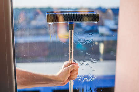 Window cleaning in high-rise buildings, houses with a brush. Window cleaning brush. Large window in a multi-storey building, cleaning service. Dust removal and glass washing.