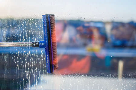 Window cleaning brush. Large window in a multi-storey building, cleaning service. Window cleaning in high-rise buildings, houses with a brush. Dust removal and glass washing.