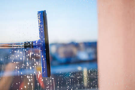 Window cleaning brush. Large window in a multi-storey building, cleaning service. Window cleaning in high-rise buildings, houses with a brush. Dust removal and glass washing. Imagens
