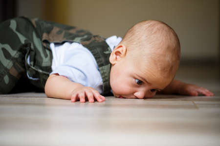 little boy aged 8 months in overalls, a white shirt and white socks crawling on the floor and smiling