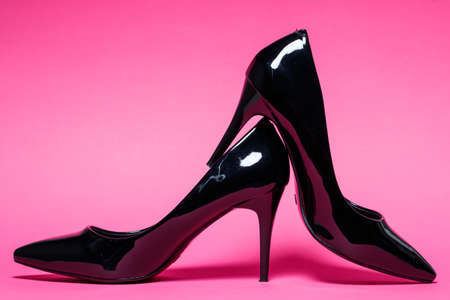 Black patent leather pumps on a colored background