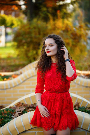 girl with curls in a red dress on an autumn city alley Stock Photo