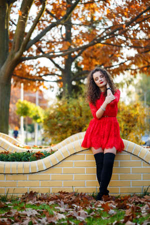 girl with curls in a red dress on an autumn city alley Imagens