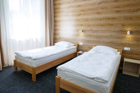 Large bright room in a hostel with three beds. White bedding Stock Photo