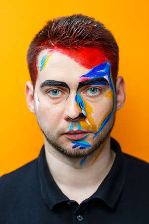 Makeup on the skin. Portrait of a young man with colored paint on a yellow background. Professional Makeup Fantasy Art Makeup