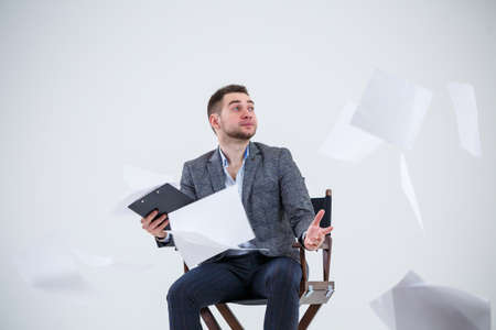Business man businessman in a suit sitting on a wooden chair and throws documents. On a white background with thoughts of a new project Stok Fotoğraf
