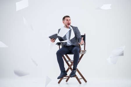 Business man businessman in a suit sitting on a wooden chair and throws documents. On a white background with thoughts of a new project