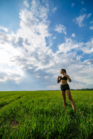 Healthy lifestyle concept. Young attractive woman in sportswear does stretching her hand before training on the nature against a blue sky. Muscle warming