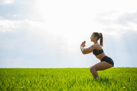 Girl athlete does squats in nature, exercises for the buttocks. Young woman go in for sports, healthy lifestyle, athletic body. She is in sportswear, black top and shorts.