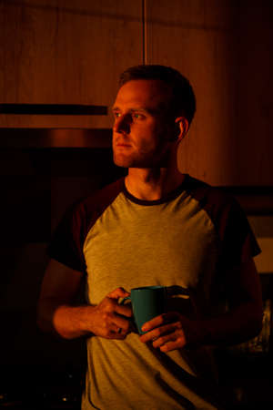 A man standing in front of a window in sunset lighting is drinking coffee in his kitchen