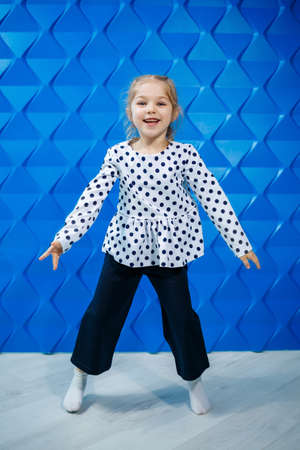 A blonde girl of 7 years old in a jacket with peas on a blue background dances and laughs, bright children's emotions of joy, a happy childhood
