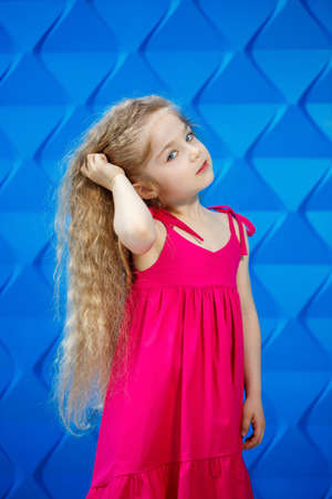 Fair-haired little girl in a pink dress on a blue background dancing and laughing, bright children's emotions of joy, happy childhood