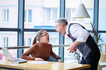 Girl business lady sitting at a wooden table with a laptop and working teacher boss mentor indicates her mistakes. Screams and hits the table with his hand Foto de archivo