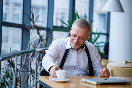 Adult male manager businessman worked successfully and at the end of the day drinks coffee without a jacket
