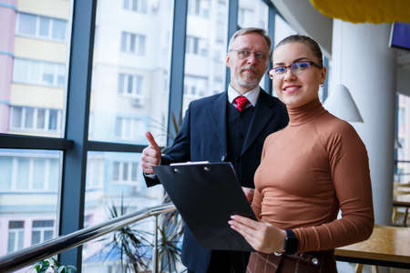 Girl manager in her own office tells a successful new business plan for economic development to her teacher mentor boss. Holds a folder with important documents in his hands.