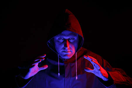 A man in a protective suit in a dark room. Halloween image concept. Virus protection. Illuminated with colored lights