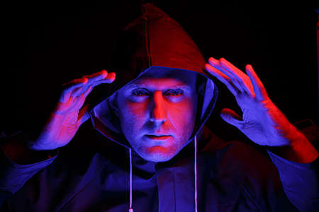 A man in a protective suit in a dark room. Halloween image concept. Illuminated with colored lights