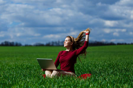 Joyful young girl on the grass with a laptop on her lap. He raised his hands up and laughed. Happiness in the lifestyle of a classical student. Work on the nature. Rest after a good working day.