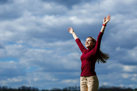 Joyful young girl on a background of the sky with clouds. He raised his hands up and laughed. Happiness in lifestyle. Inspiration in nature. Rest after a good working day.