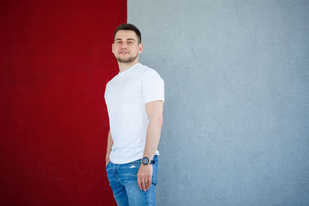 Stylish young man, a man dressed in a white blank t-shirt standing on a gray and red wall background. Urban style of clothes, modern fashionable image. Men's fashion 免版税图像