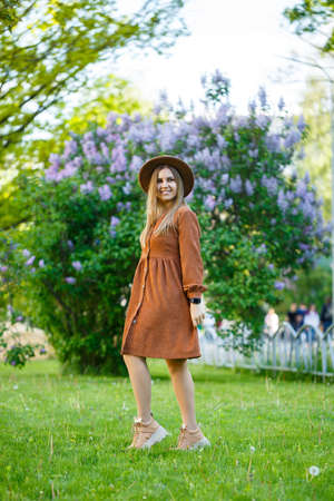 stylish girl in a brown hat and a light dress on a background of lilac lush bushes. Young woman with a smile on her face on a sunny summer day walks in the park